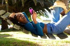 Szczęśliwa młoda kobieta słucha muzyka z telefonem komórkowym Zdjęcia Royalty Free