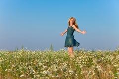 Szczęśliwa młoda kobieta skacze w polu rumianki. Portret w słonecznym dniu Fotografia Royalty Free