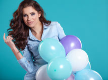Szczęśliwa młoda kobieta stoi nad błękit ścianą i trzyma balony obraz stock
