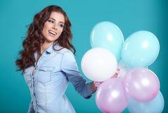 Szczęśliwa młoda kobieta stoi nad błękit ścianą i trzyma balony fotografia stock