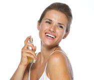 Szczęśliwa młoda kobieta stosuje pachnidło obraz royalty free