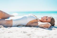 Szczęśliwa młoda kobieta sunbathing na piaskowatej plaży w swimsuit Obrazy Stock