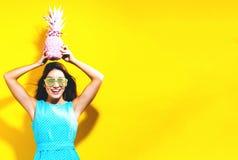 Szczęśliwa młoda kobieta trzyma ananasa zdjęcie royalty free