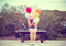 Szczęśliwa młoda kobieta trzyma kolorowych balony i obsiadanie na ławce Zdjęcia Stock
