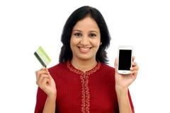 Szczęśliwa młoda kobieta trzyma mądrze telefon i kredytową kartę Zdjęcie Royalty Free