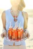 Szczęśliwa młoda kobieta trzyma naczynie z przy zmierzchu przyjęciem napoje Zdjęcie Royalty Free