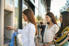 Szczęśliwa młoda kobieta używa gotówkową maszynę Kobiety używa kredytową kartę Fotografia Royalty Free