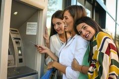 Szczęśliwa młoda kobieta używa gotówkową maszynę Kobiety używa kredytową kartę Fotografia Stock