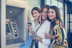 Szczęśliwa młoda kobieta używa gotówkową maszynę Kobiety używa kredytową kartę L Obrazy Royalty Free