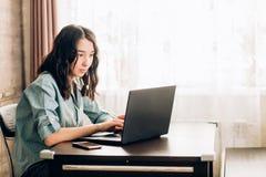 Szczęśliwa młoda kobieta używa laptop w domu obrazy royalty free
