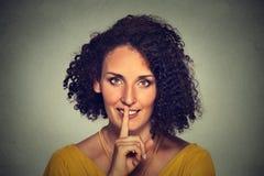 Szczęśliwa młoda kobieta umieszcza palec na wargach pyta shhhhh, zaciszność, cisza obrazy stock