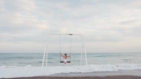 Szczęśliwa młoda kobieta w białej swimsuit jazdie na huśtawkowym cieszy się dennym widoku pi?kni poj?cia basenu wakacje kobiety p zbiory