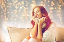 Szczęśliwa młoda kobieta w ciepłym pulowerze w domu obrazy royalty free