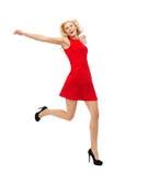 Szczęśliwa młoda kobieta w czerwieni sukni skokowej wysokości Fotografia Stock
