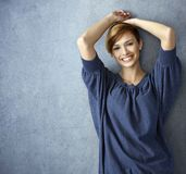 Szczęśliwa młoda kobieta w niebieskich dżinsach pozuje przy ścianą obraz stock