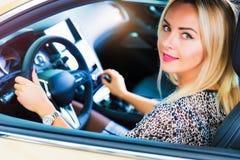 Szczęśliwa młoda kobieta w nowożytnym luksusowym samochodzie Obraz Stock
