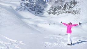 Szczęśliwa młoda kobieta w różowej narciarskiej kurtce, rękawiczkach, kapeluszu i narciarskich butach, fotografia stock