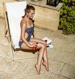 Szczęśliwa młoda kobieta w sunbed stosuje słońce bloku podczas gdy siedzący Zdjęcia Stock