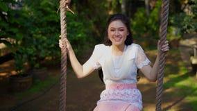 Szczęśliwa młoda kobieta w Tajlandzki tradycyjny smokingowy relaksować na drewnianej huśtawce zbiory