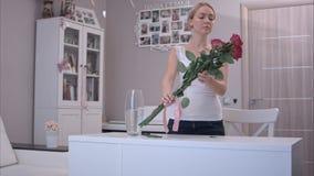 Szczęśliwa młoda kobieta wiąże tasiemkowego łęk na czerwieni róży bukiecie i wącha je Zdjęcia Royalty Free