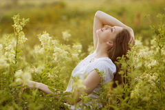 Szczęśliwa młoda kobieta wysocy wildflowers Fotografia Royalty Free