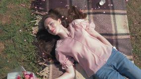 Szczęśliwa młoda kobieta z bieżącym włosy kłama blisko pięknego bukieta kwiaty na bedspread na łące i cieszy się plenerowego zbiory wideo
