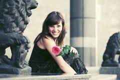 Szczęśliwa młoda kobieta z czerwieni różą w miasto ulicie Obrazy Stock