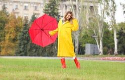 Szczęśliwa młoda kobieta z czerwonym parasolem w parku zdjęcie royalty free