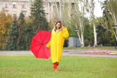 Szczęśliwa młoda kobieta z czerwonym parasolem w parku fotografia stock