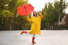 Szczęśliwa młoda kobieta z czerwonym parasolowym jest ubranym żółtym deszczowem fotografia stock