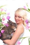 Szczęśliwa młoda kobieta z Easter tulipanami i królikiem Zdjęcie Royalty Free