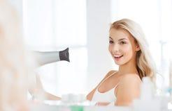Szczęśliwa młoda kobieta z fan suszarniczym włosy przy łazienką Obraz Stock