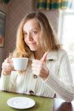 Młoda kobieta z filiżanką kawy w ręce pokazuje kciuk up podpisuje Obrazy Royalty Free