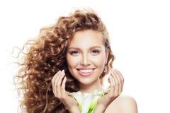 Szczęśliwa młoda kobieta z kędzierzawym włosy odizolowywającym na bielu Piękny model z jasną skórą i kwiaty w ręka portrecie zdjęcia stock
