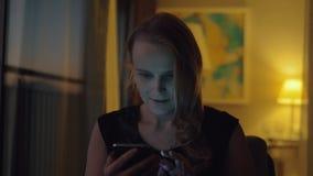 Szczęśliwa młoda kobieta z komórką w wieczór w domu zbiory wideo