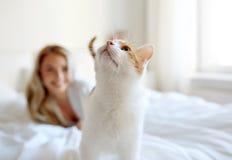 Szczęśliwa młoda kobieta z kotem w łóżku w domu Zdjęcia Stock