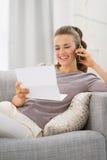 Szczęśliwa młoda kobieta z listowym opowiada telefonem komórkowym Fotografia Stock
