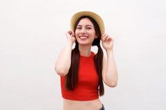 Szczęśliwa młoda kobieta z oba rękami na kapeluszu fotografia stock