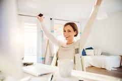 Szczęśliwa młoda kobieta z outstretchced rękami indoors, pracujący w ministerstwo spraw wewnętrznych obraz royalty free