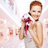 Szczęśliwa młoda kobieta z prezentem urodzinowym w rękach Obrazy Stock