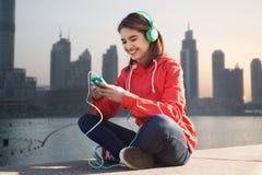 Szczęśliwa młoda kobieta z smartphone i hełmofonami Zdjęcia Stock