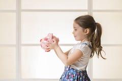Szczęśliwa młoda mała dziewczynka z prosiątko bankiem Obraz Stock