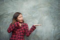 Szczęśliwa młoda modniś kobieta przedstawia kopii przestrzeń na jej palmie, aga Zdjęcie Royalty Free
