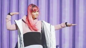 Szczęśliwa młoda ostra kobieta z różowym włosianym tanem na coloured tle Piękna kobieta tanczy blisko purpurowego zbiornik zbiory wideo