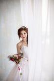 Szczęśliwa młoda panna młoda z ślubnym bukietem blisko okno, pionowo fotografia Obraz Stock