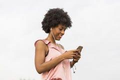 Szczęśliwa młoda piękna afro amerykańska kobieta słucha muzyka wewnątrz Zdjęcia Royalty Free