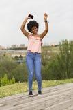 Szczęśliwa młoda piękna afro amerykańska kobieta słucha muzyka wewnątrz Obraz Stock