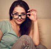 Szczęśliwa młoda przypadkowa kobieta w szkłach na kanapie Zdjęcie Royalty Free