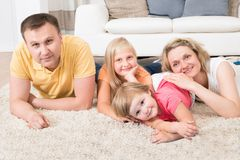 Szczęśliwa młoda rodzina kłaść na dywanie Fotografia Stock