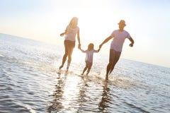 Szczęśliwa młoda rodzina ma zabawa bieg na plaży przy zmierzchem obraz stock